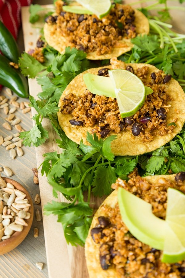 Healthy vegan taco filling on three corn tostados with vegan cheese sauce and chopped greens on a wood board