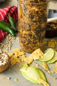 Vegan taco filling in a mason jar with crumbled corn chips, sliced limes, and sunflower seeds and vegetables next to the jar
