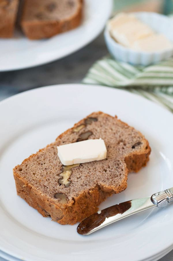 A slice of banana bread with a pat of butter on top on a white plate with a butter knife on the side of the plate and a plate of bread in the background with a green striped towel and a white dish of butter