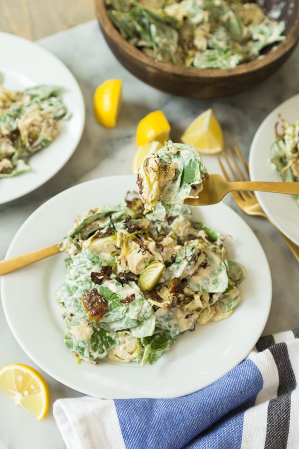 Brussels sprouts salad with mixed greens covered in Caesar dressing on a white plate with a gold fork full of salad and two white plates with salad on the sides and lemon wedges