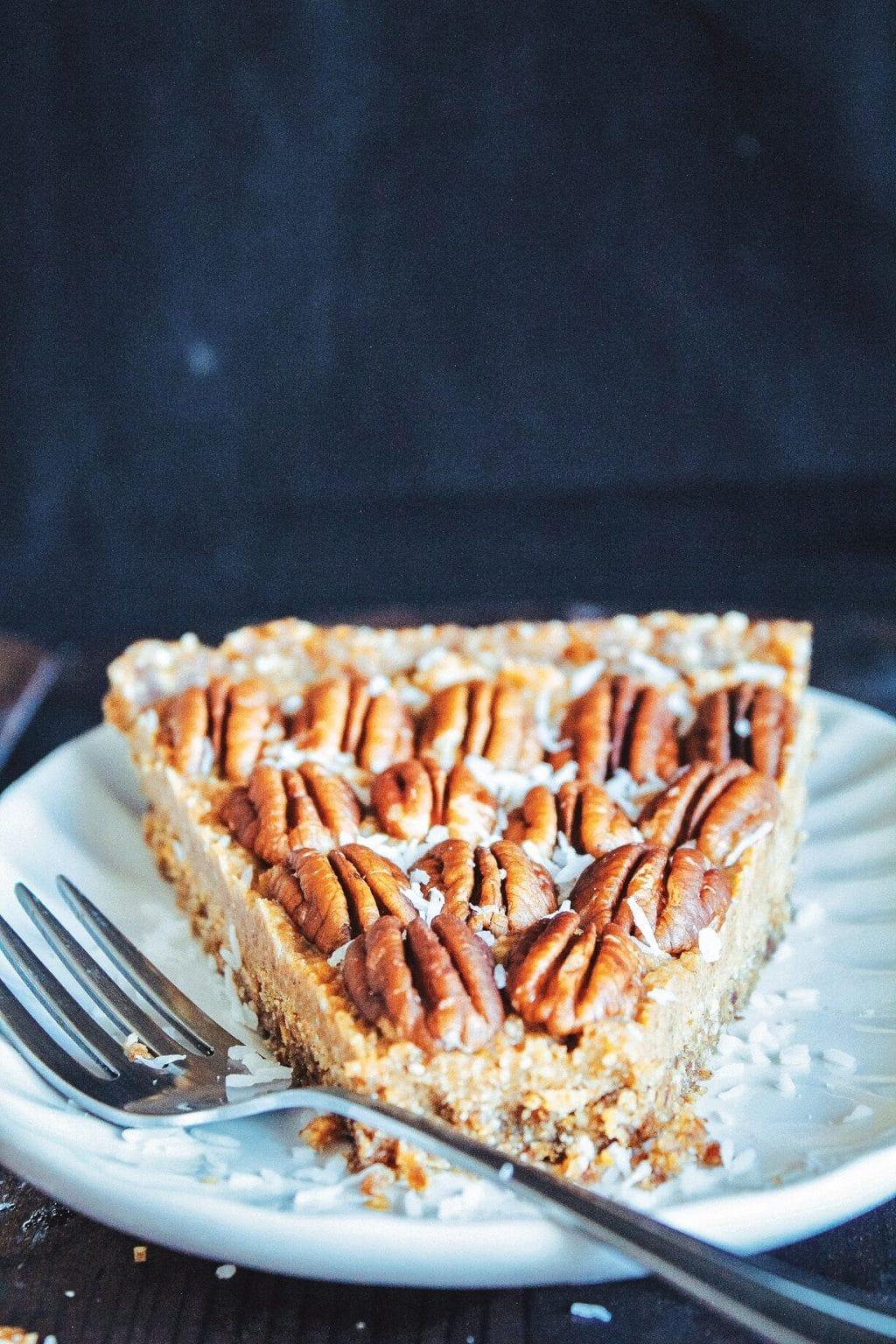 A slice of maple pecan pie on a white plate with a silver fork resting on the edge of the plate