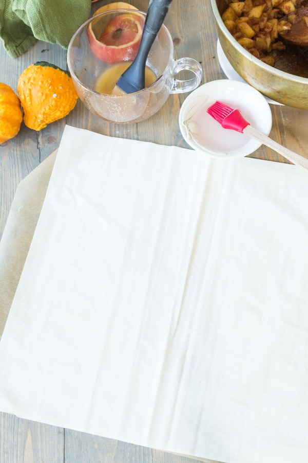 Two pieces of phyllo dough on parchment paper with a small white bowl of water and a red pastry brush next to it