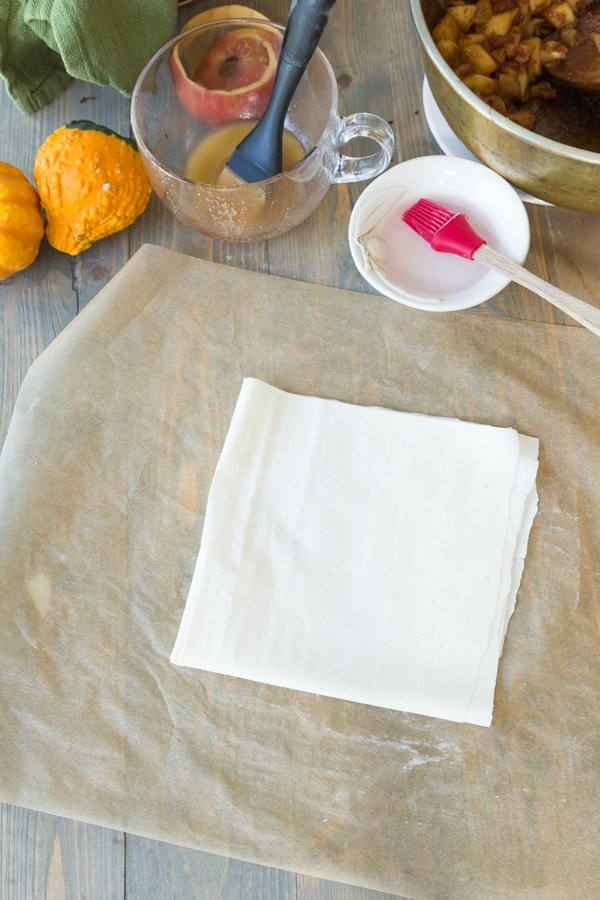 A square of phyllo dough on parchment paper for apple turnovers