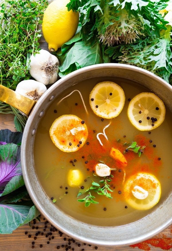 A pot of vegetable broth with lemons, garlic, turmeric, fresh herbs and peppercorns floating on top