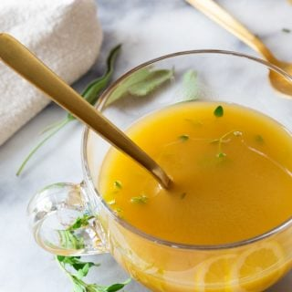 Broth in a clear glass mug with a gold spoon and herbs and lemon slices on a marble board
