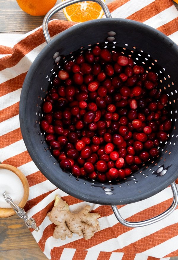 A large gray strainer with fresh cranberries in it on an orange and white striped towel and a wood bowl of sugar and a knob of ginger next to it