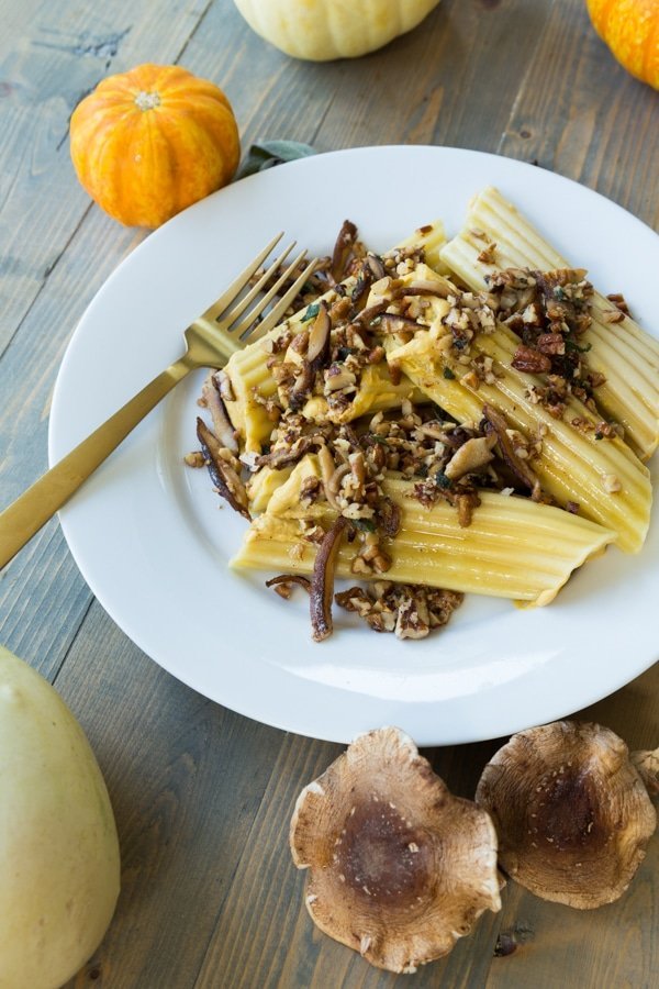 A stack of pumpkin manicotti on a white plate with mushrooms, pecans, and a brown butter sauce on top and a gold fork on the plate with shiitake mushrooms and pumpkins on the side of the plate