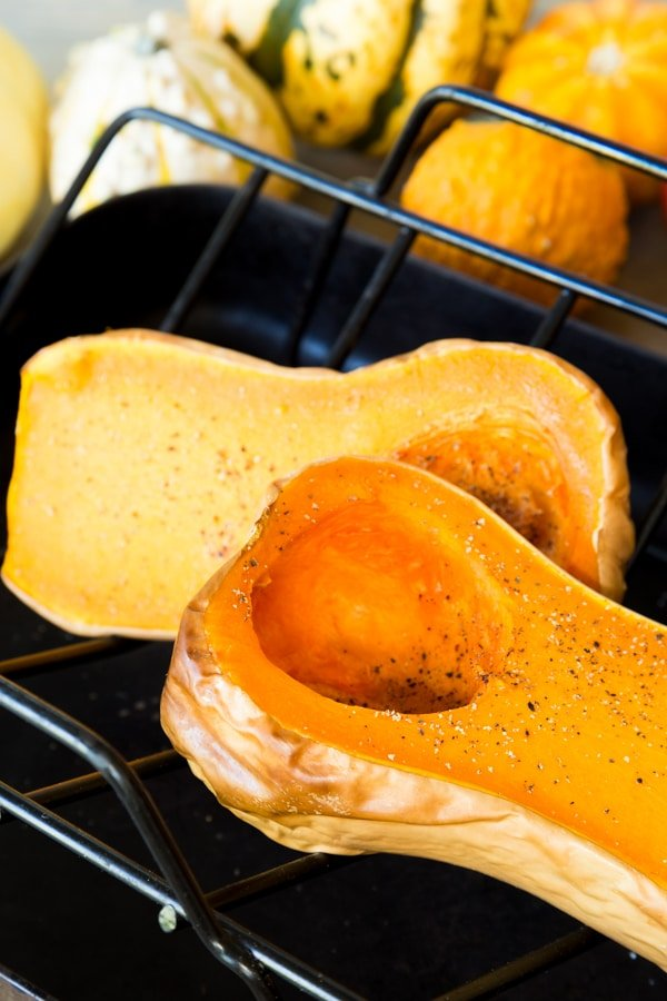 Roasted butternut squash with salt and pepper on a roasting tray