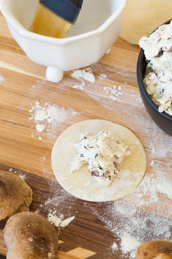 Wonton with a tablespoon of ricotta shiitake filling in the middle of the wood board