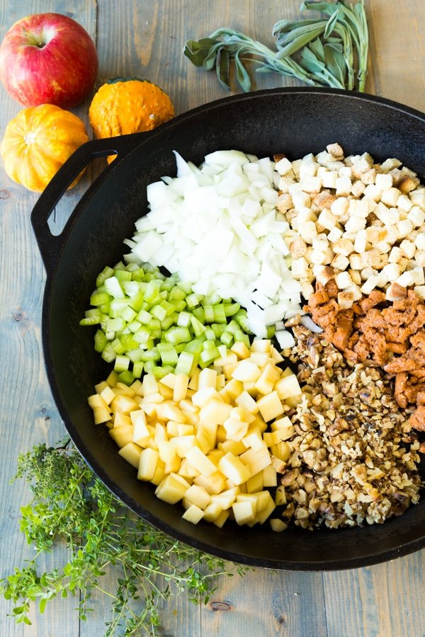 Onions, celery, breadcrumbs, herbs, apples, and breadcrumbs for stuffing in an iron skillet with ingredients on the side of the pan