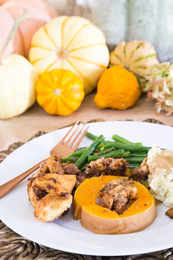 Thanksgiving plate of green beans, stuffed butternut squash, stuffing, gravy, and mashed potatoes