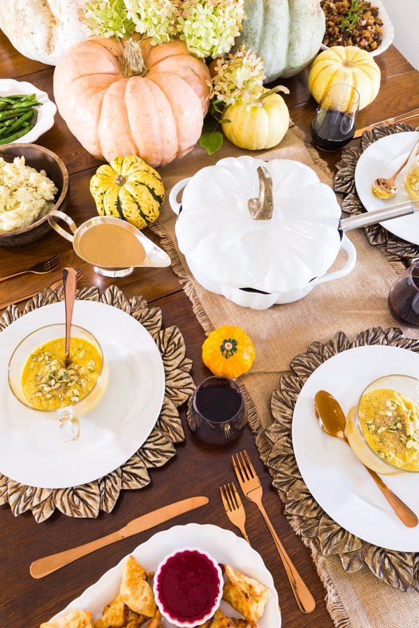 Thanksgiving table setting with white place, leaf chargers, copper flatware, and pumpkins