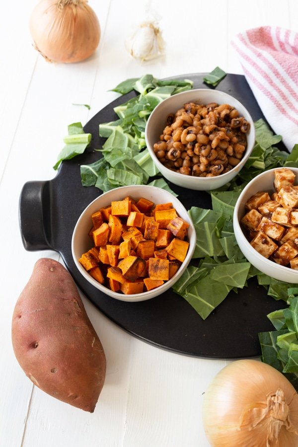 A round black serving platter with three white bowls of BBQ vegetables and a sweet potato and greens next to it.