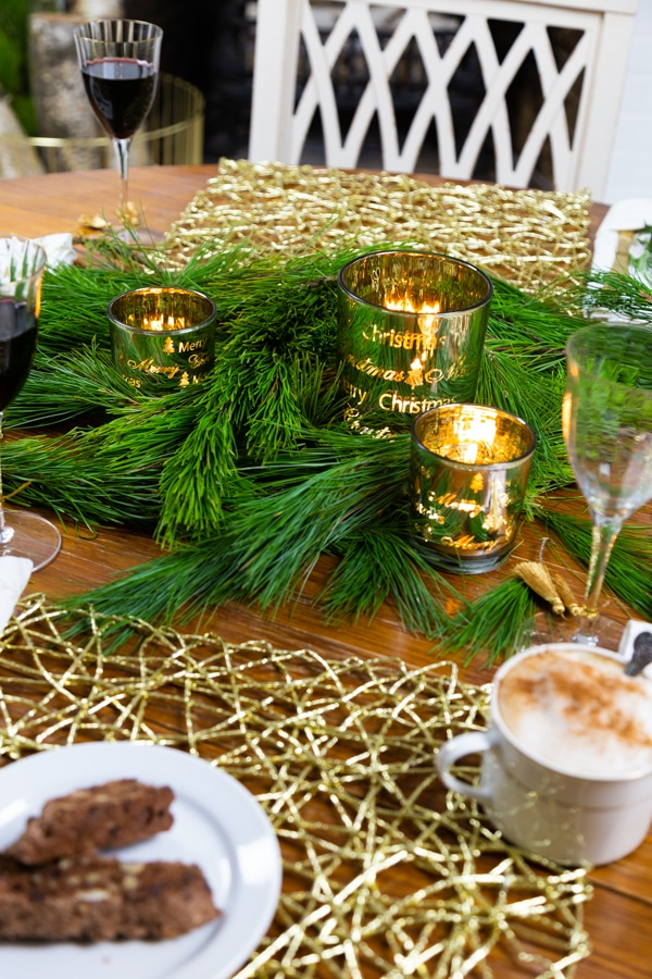 Pine branches with gold votives and a gold place mat with a white plate of cookies and a white cup of coffee