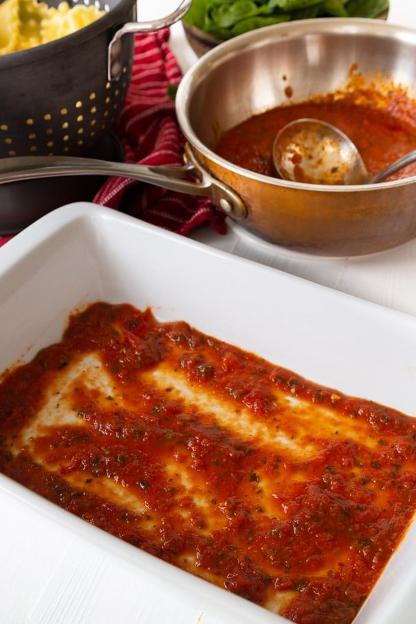 A white ceramic pan with red sauce and lasagna noodles and a copper pot in the background with sauce.