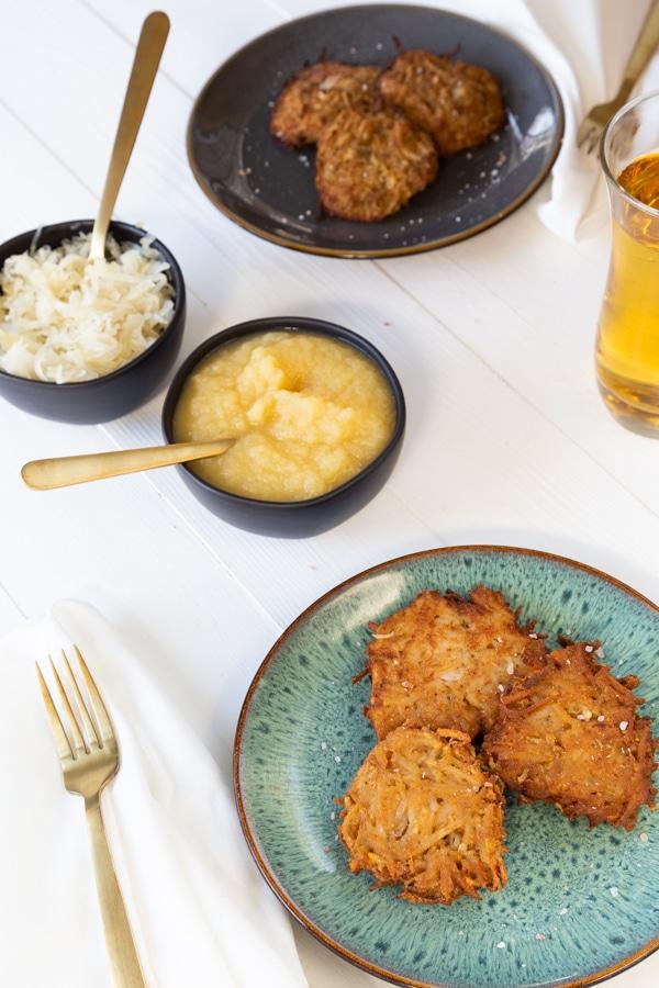 Potato Pancakes on blue plates with apple sauce, sauerkraut on a white board