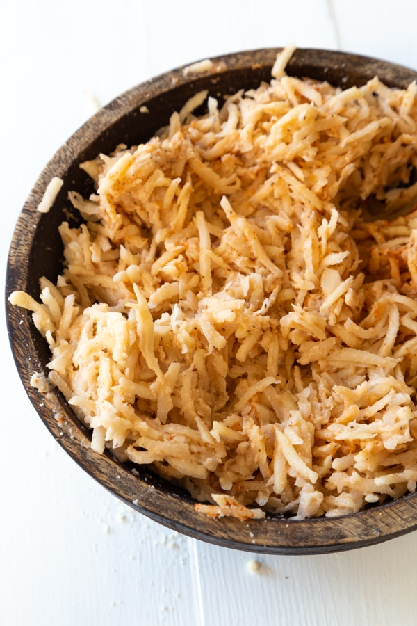 Potato pancake ingredients all mixed into a wood bowl on a white wood background