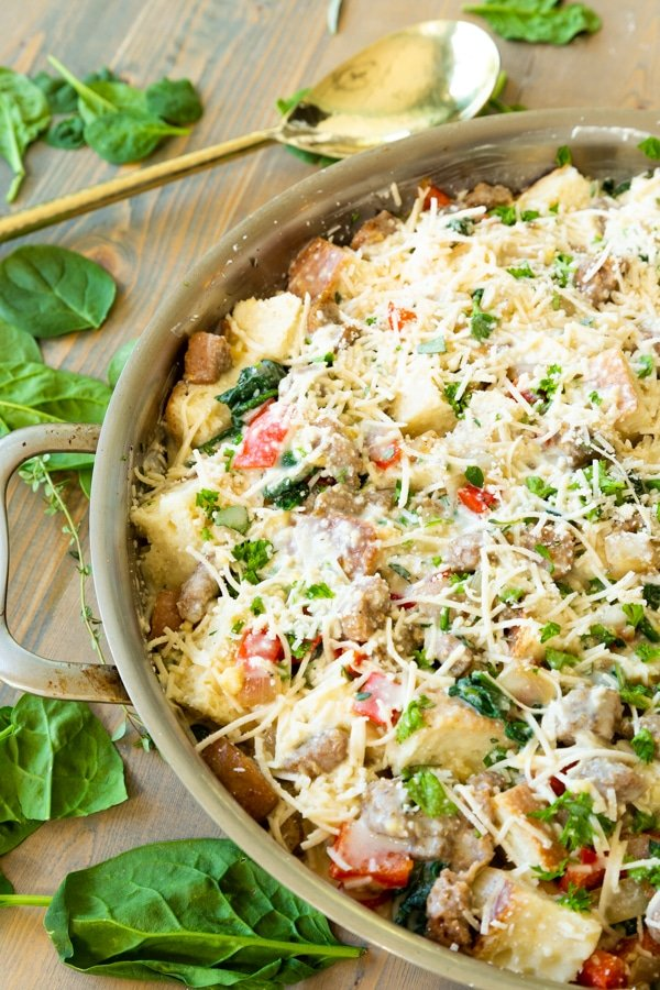 Unbaked vegan strata in a copper round pan with herbs and garlic scattered around it.