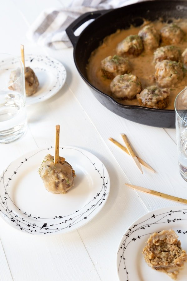 Several small white plates with black birds on the rim and a single Swedish meatball with a toothpick on each plate and a cast-iron skillet filled with vegan Swedish meatballs in the background.