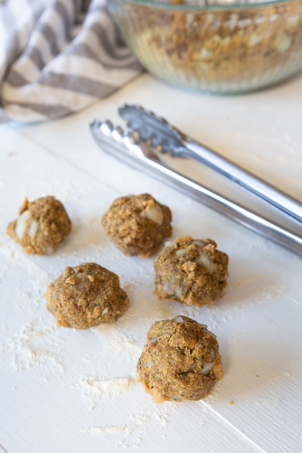 Uncooked vegan Swedish meatballs on a white board with silver tongs and a blue and white dish towel next to them