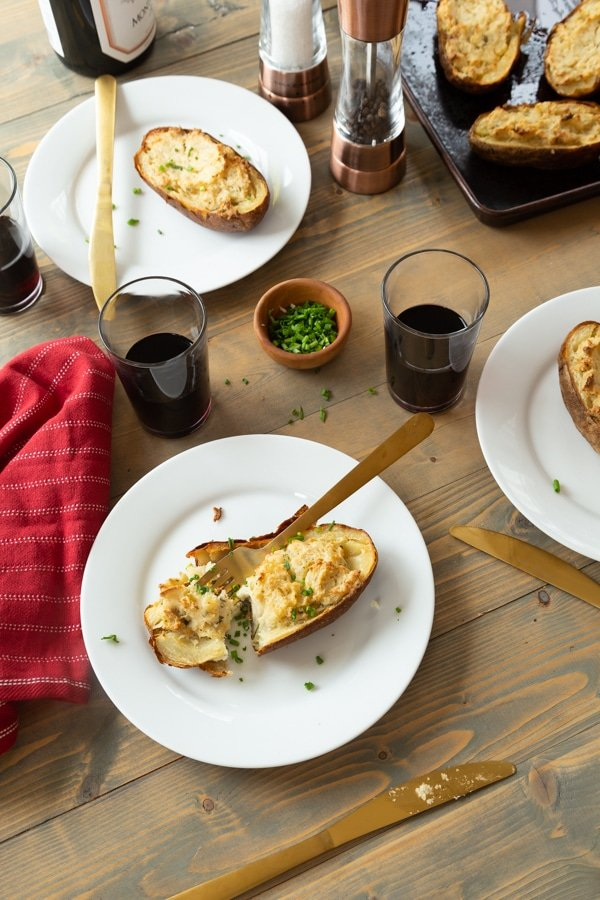 Twice baked ranch potatoes on a wood board with white plates, chives, and glasses of red wine