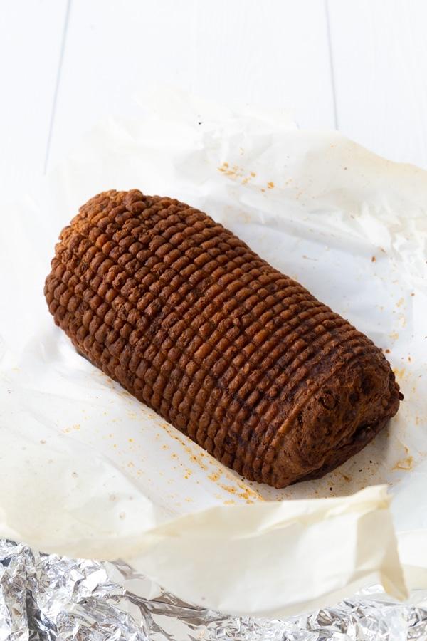 A baked Field Roast Celebration Roast on a piece of white parchment paper
