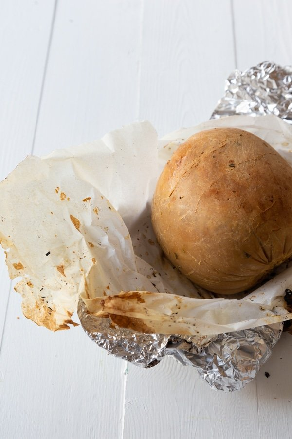 A roasted Tofurky Veggie Roast on a piece of foil and white parchment paper