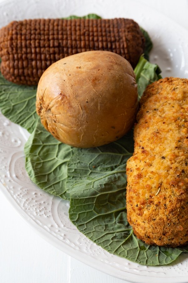 Three vegan turkey roasts on a white platter on greens,.