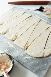 vegan croissant dough cut into triangles on marble