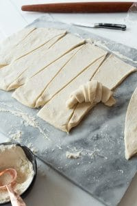 vegan croissant dough being rolled into a crescent shape on marble