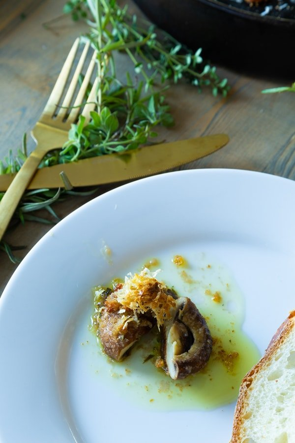 A roasted garlic mushroom on a white plate with a piece of bread and a gold knife and fork and sprigs of fresh thyme next to the plate.