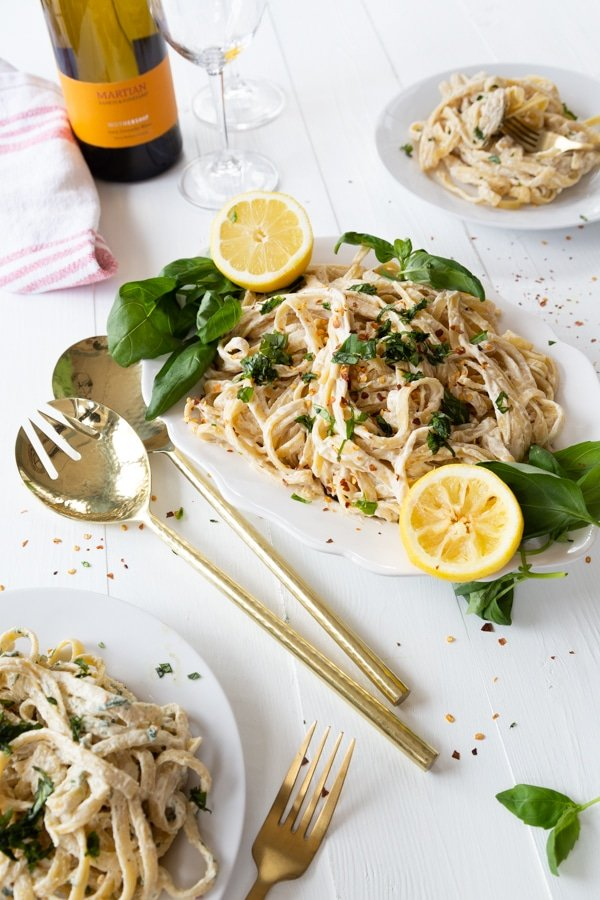 A white platter of vegan Fettuccine Alfredo with basil and lemons on a white wood table and two plates of the Alfredo and a bottle of wine and gold serving utensils