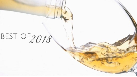 """White wine being poured into a glass and the text, """"Best of 2018"""" in black on a white background"""