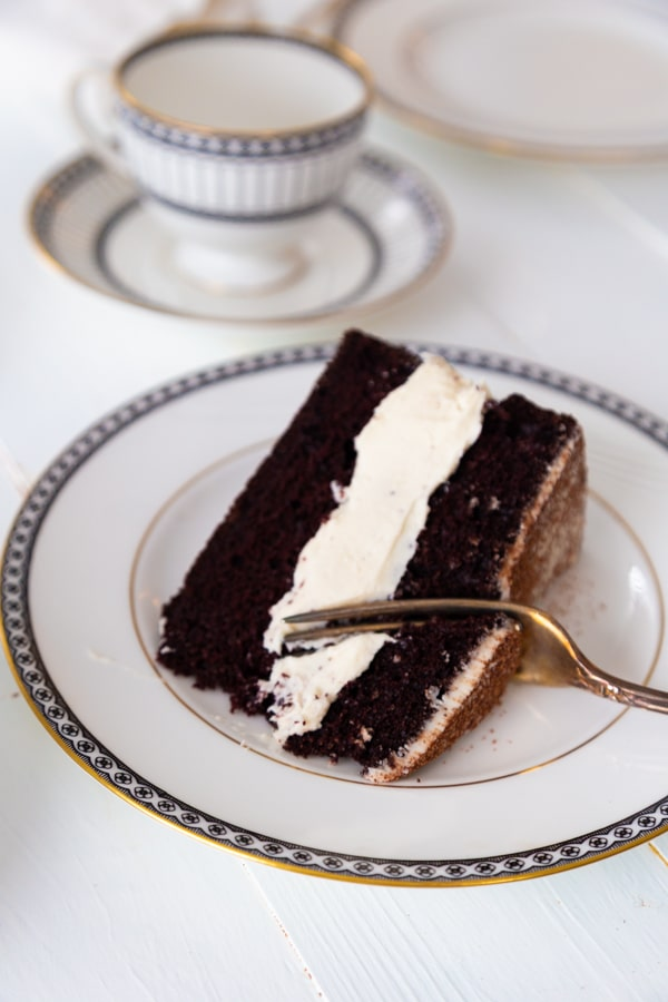 A slice of chocolate cake with vanilla frosting on a white plate with a silver fork cutting into it.
