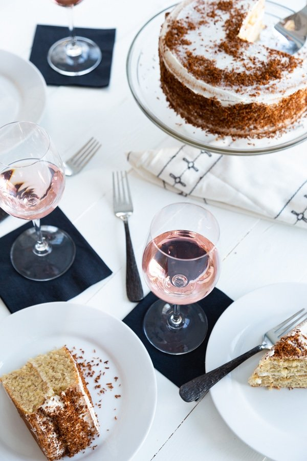 A white table with glasses of rose and a cake and white plates with slices of cake.