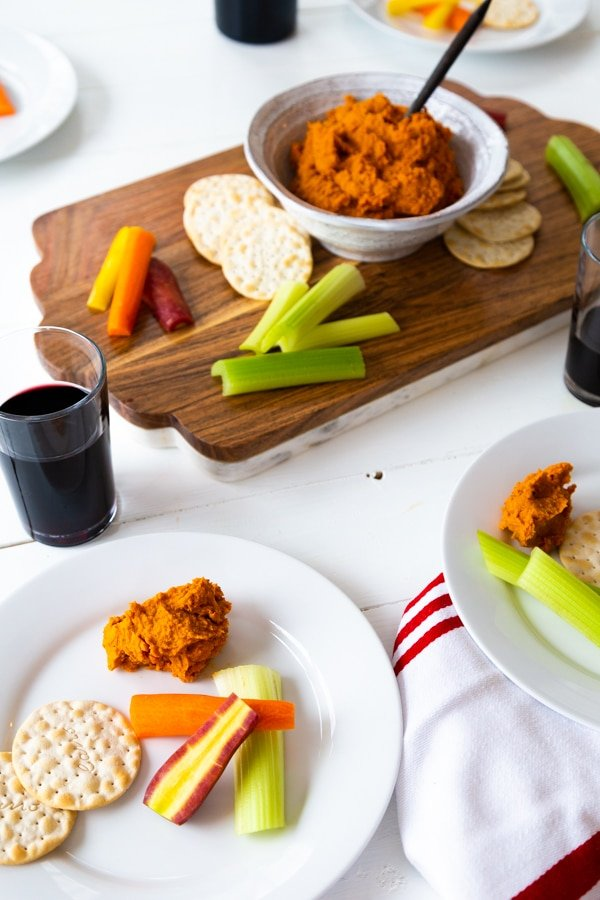 A wood and marble board with a white bowl of curry dip and vegetables and crackers and two white plates with some dip, crackers and vegetables with two glasses of red wine.