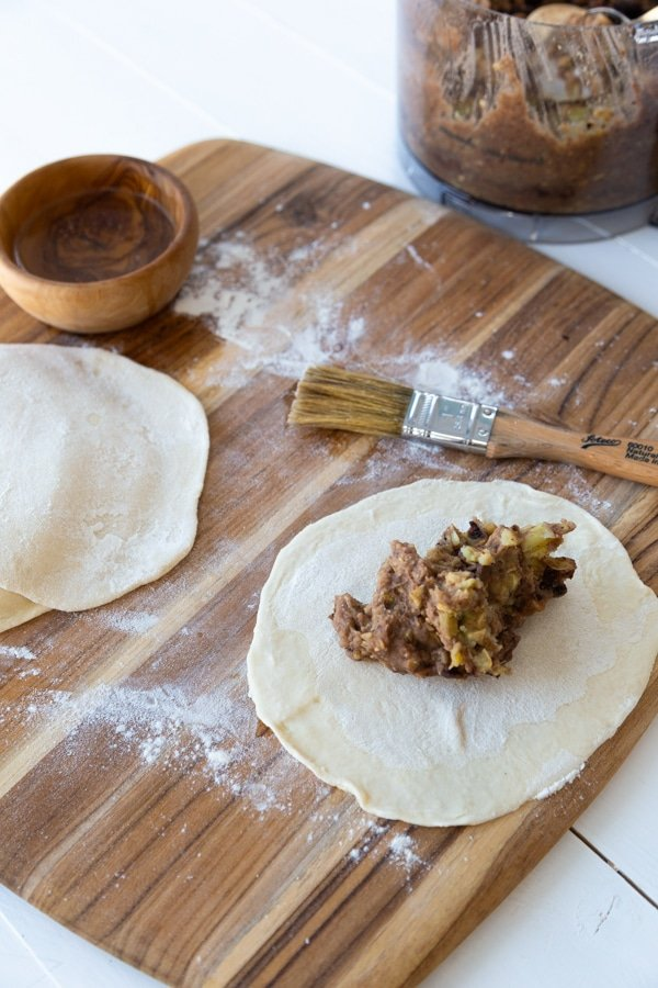 round empanada dough being filed with sweet potato and beans