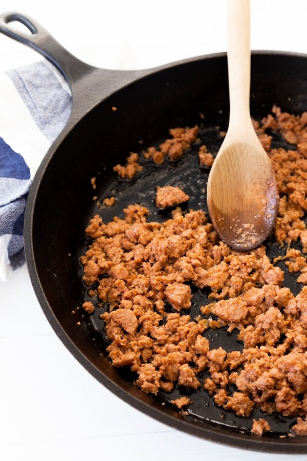 Cooking ground sausage in an iron skillet with a wood spoon