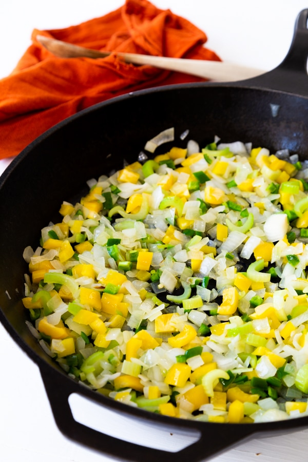 Onions, celery, and peppers cooking in a cast-iron skillet