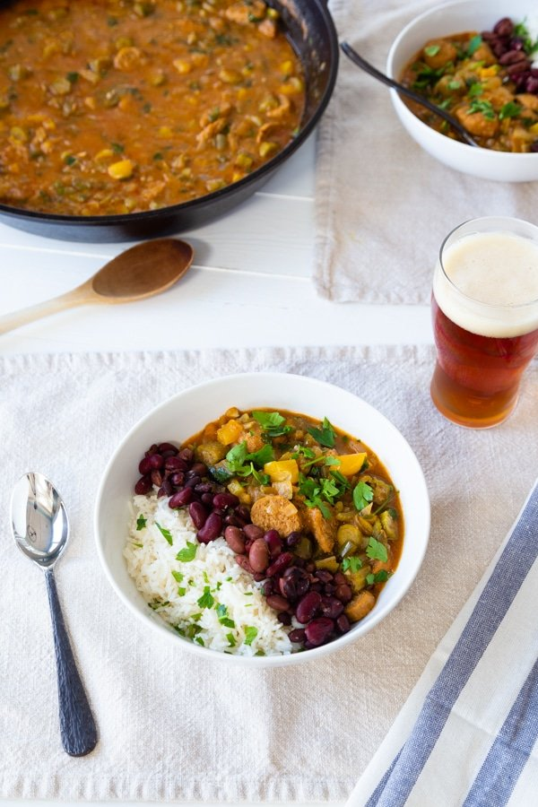 An iron skillet with gumbo and two white bowls with gumbo, rice, and beans with a glass of beer and napkins and utensils on the table