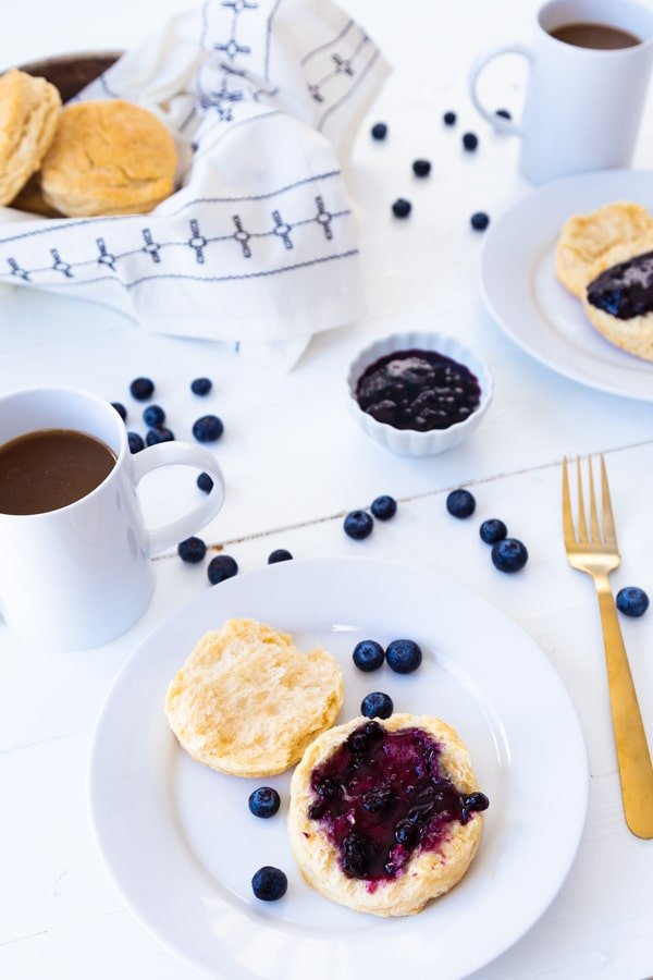 A white plate with a biscuit covered in blueberry jam with a basket of biscuits, a mug of coffee, and a small bowl of blueberries and scattered blueberries on the table
