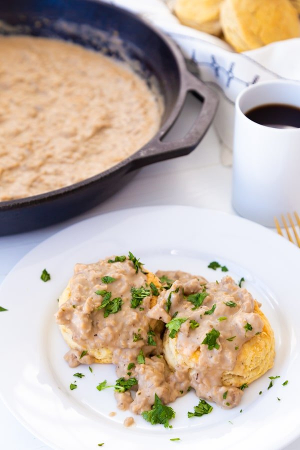Biscuits and gravy on a white plate with a cup of coffee and a skillet of gravy in the background