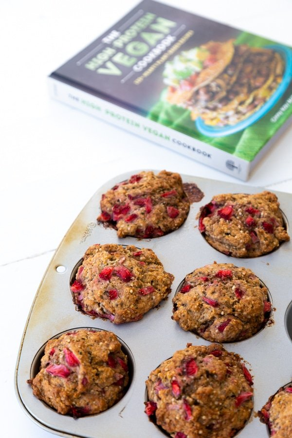 Strawberry muffins in a muffin pan with The High-Protein Vegan Cookbook next to the pan.