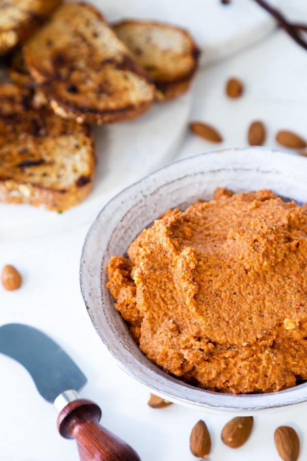 A white bowl of red pepper dip with a wood spread knife and almonds and toast next to the bowl.