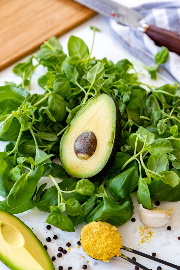Half of an avocado on top of a pile of basil leaves with lemon, garlic, nutritional yeast, and rock salt and peppercorns.