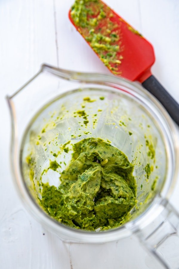 Pesto in a blender with a red and black spatula with oil-free pesto on it on a white board.