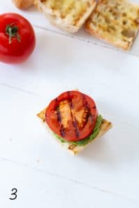 caprese sandwich with basil on top and grilled tomato on a white board