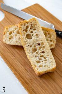 bread cut in half on a wood cutting board with serrated knife