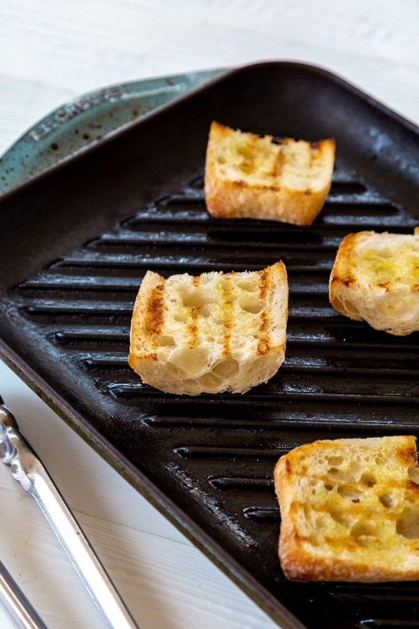 Grilled bread on a grill pan being used for our mini vegan caprese pesto sandwiches.
