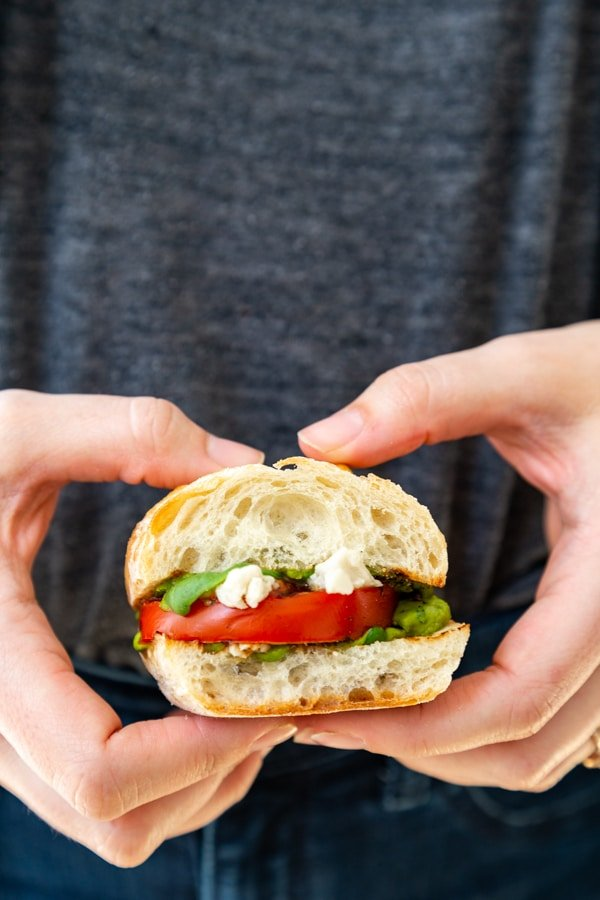 Two hands holding one of our vegan pesto caprese salad sandwiches.